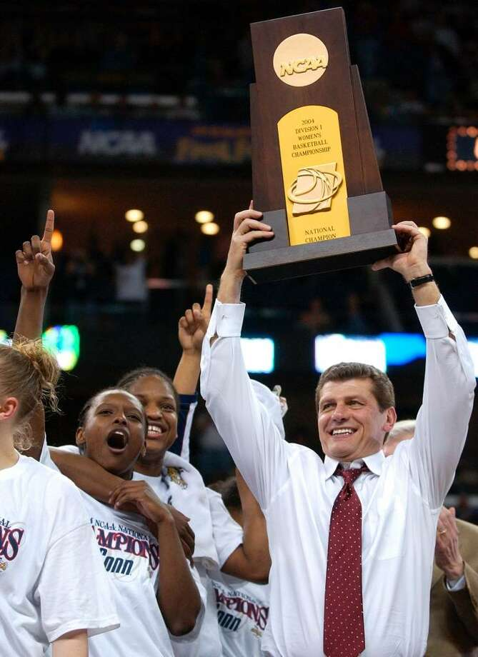 Connecticut coach Geno Auriemma hoists the championship trophy after UConn beat Tennessee 70-61 in the NCAA Division 1 Women's championship game Tuesday, April 6, 2004, in New Orleans. (AP Photo/Mark Humphrey) Photo: MARK HUMPHREY, AP / AP