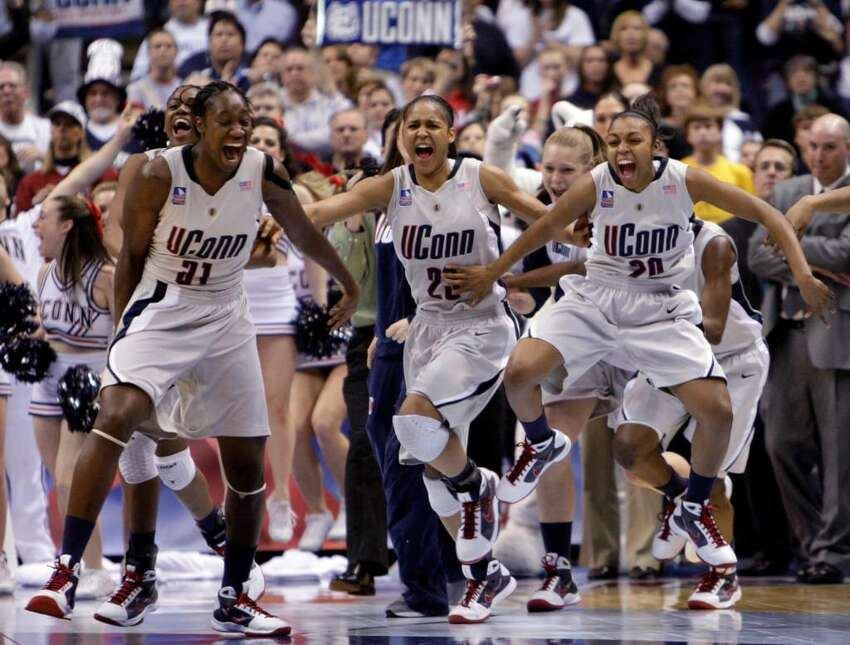 Connecticut's Tina Charles, Maya Moore and Renee Montgomery, from left in front, celebrate Connecticut's win in the championship game at the women's NCAA college basketball tournament Final Four on Tuesday, April 7, 2009, in St. Louis. Connecticut won 76-54. (AP Photo/Mark Humphrey)