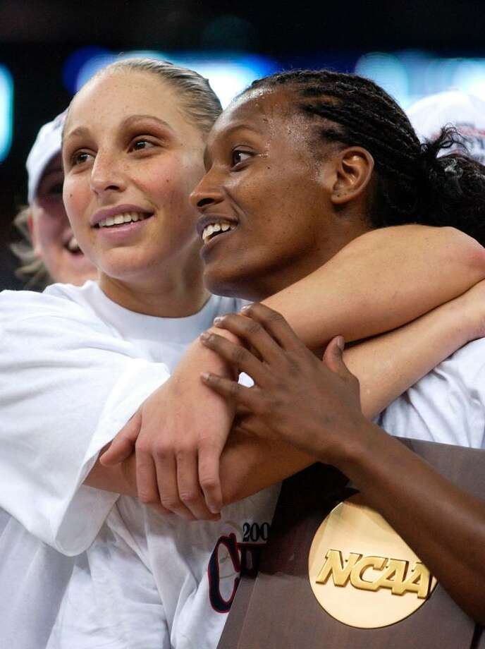 ** CORRECTS ID OF PLAYER AT RIGHT TO ASHLEY BATTLE, NOT JESSICA MOORE ** Connecticut's Diana Taurasi, left, hugs teammate Ashley Battle and the trophy after winning the NCAA Division 1 Women's championship 70-61 over Tennessee Tuesday, April 6, 2004, in New Orleans. (AP Photo/Mark Humphrey) Photo: MARK HUMPHREY, AP / AP