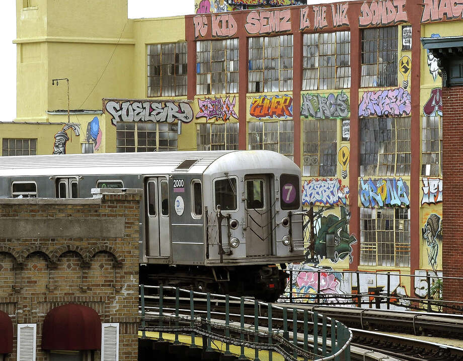 The 7 train passes by 5 Pointz, a graffiti covered  warehouse that used to house artist studios. The art of famous and novice graffiti artists covers the building's facade, all done with the encouragement of the building's owner. The building is located in the the Long Island City section of Queens. Photo: TIMOTHY A. CLARY, AFP/Getty Images / 2010 AFP