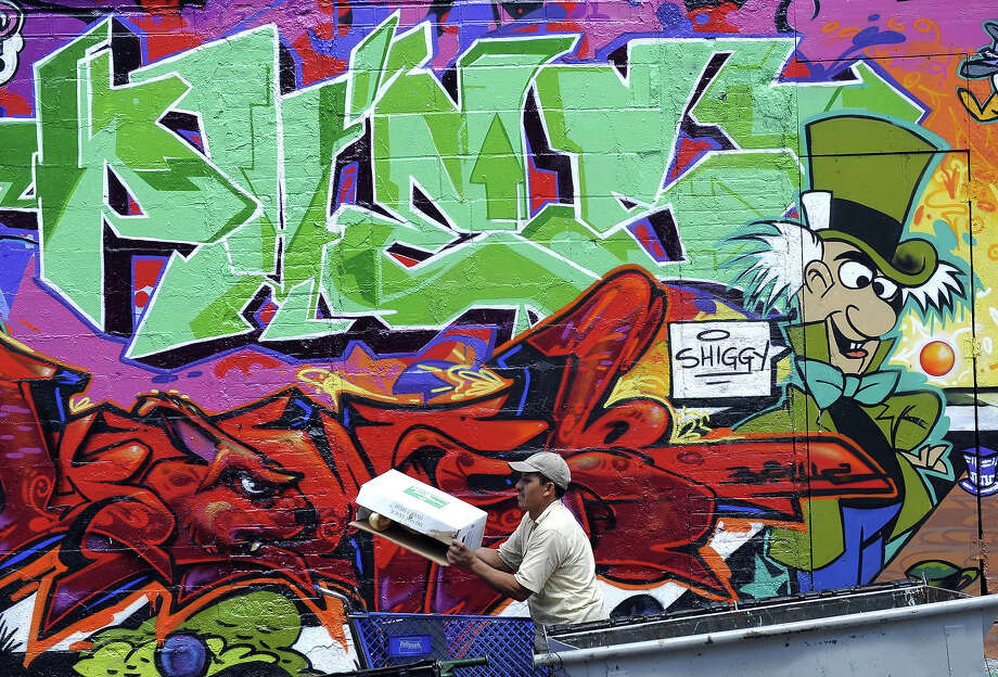 A man passes by a wall  at 5 Pointz, a graffiti covered  warehouse that used to house artist studios. Photo: TIMOTHY A. CLARY, AFP/Getty Images / 2010 AFP