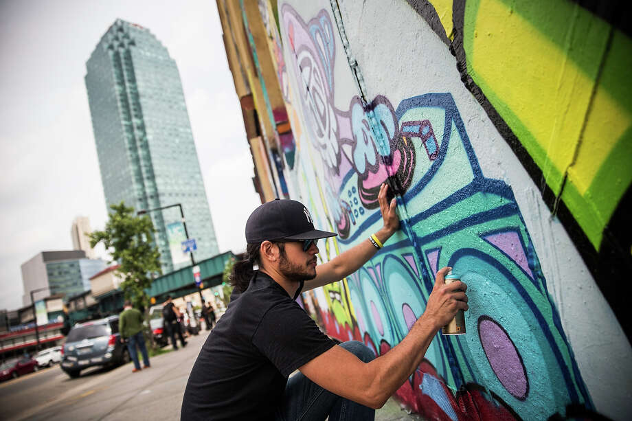 "Steve Lew, who goes by the artist name ""Kidlew,"" paints a new piece on a section of wall of the ""5 Pointz"" building on August 9, 2013 in the Long Island City neighborhood of the Queens borough of New York City. Photo: Andrew Burton, Getty Images / 2013 Getty Images"