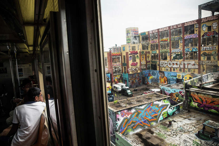 "The ""5 Pointz"" building is seen from a passing subway car on August 9, 2013 in the Long Island City neighborhood of the Queens borough of New York City. 5 Pointz is a series of properties that graffiti artists use as an outdoor art exhibit space - it is considered the Mecca of the graffiti world. The space has been used as a space for graffiti artists since the early 1990s, though in 2011, Jerry Wolkoff, the owner of the property, announced he planned to demolish the building to build high-rise residential buildings. Photo: Andrew Burton, Getty Images / 2013 Getty Images"