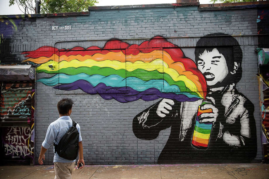 "A man walks past a mural painted on the ""5 Pointz"" building on August 9, 2013 in the Long Island City neighborhood of the Queens borough of New York City. Photo: Andrew Burton, Getty Images / 2013 Getty Images"