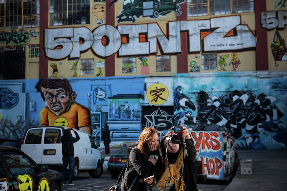 CHECK OUT MORE OF THE ART: Two women take a picture outside of the 5 Pointz Building, a landmark in the New York graffiti scene that has attracted artists from around the globe, on October 28, 2013 in the Long Island City neighborhood of the Queens borough of New York City. Photo: Andrew Burton, Getty Images / 2013 Getty Images