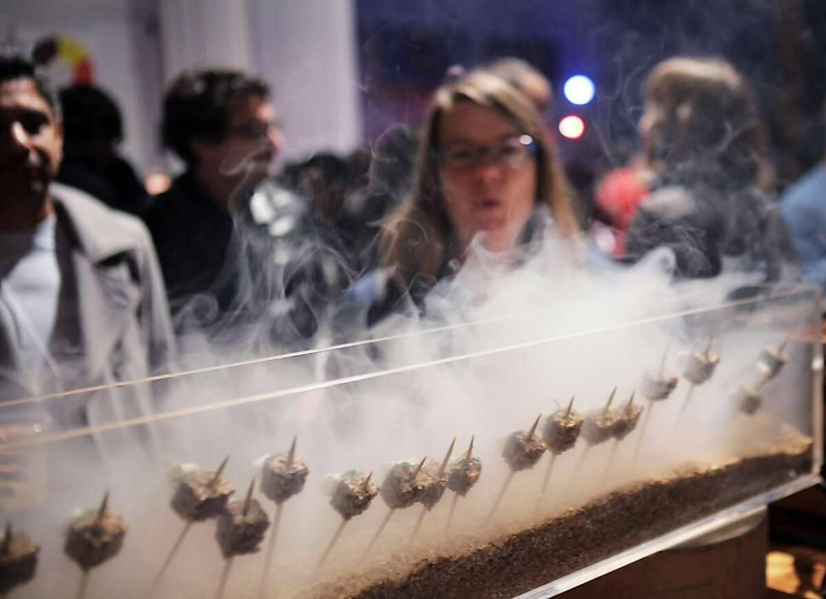 Food Hackathon participants watch as hors d'oeuvres are smoked at Tcho during an after party following the two-day event on Sunday. The world's largest food hackathon, �