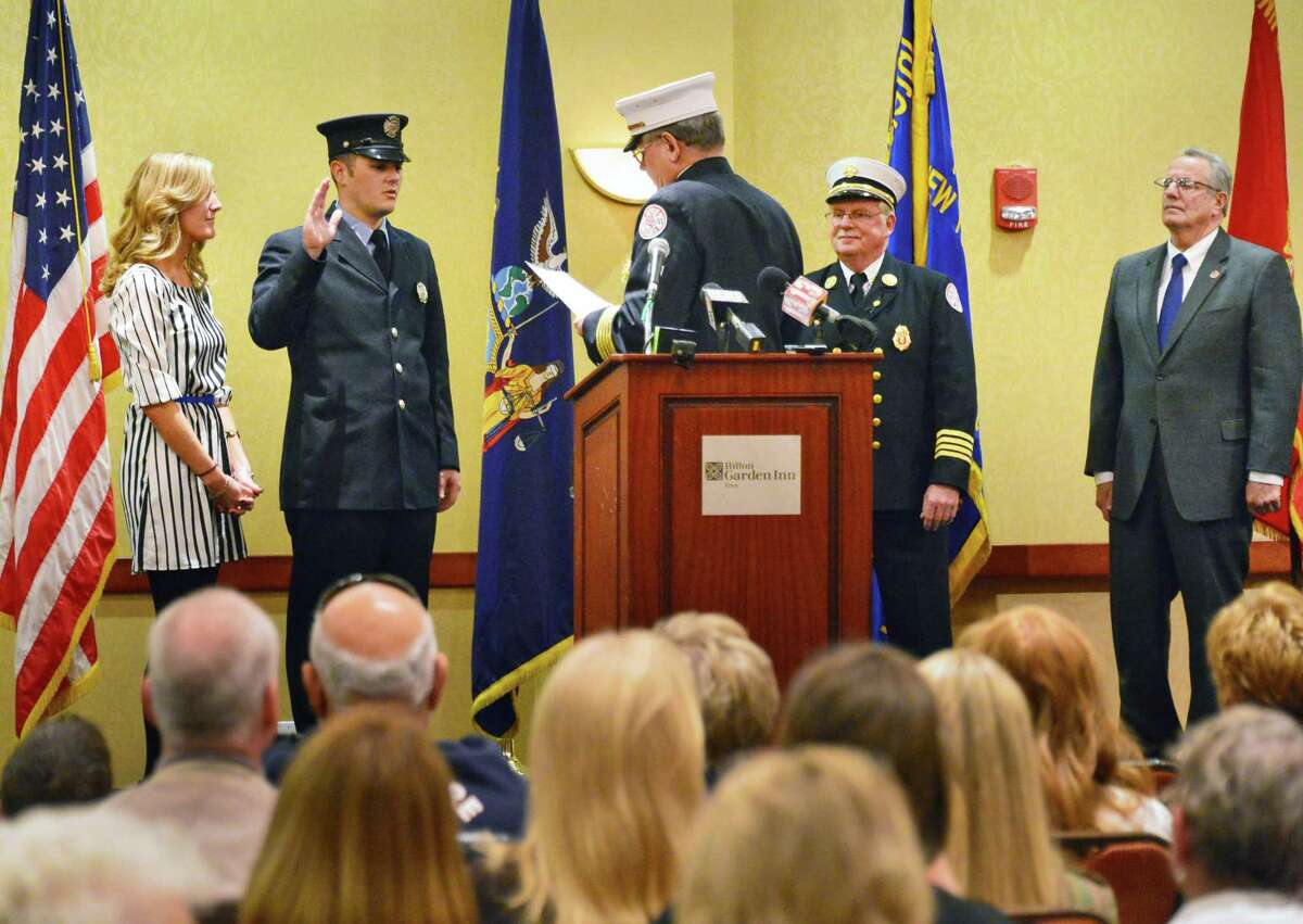 Troy Fire Department's David Bader, his wife, Vincenza, by his side, is sworn in as a lieutenant by Chief Tom Garrett, center, as during a promotion ceremony Tuesday, Nov. 19, 2013, in Troy, N.Y. (John Carl D'Annibale / Times Union)