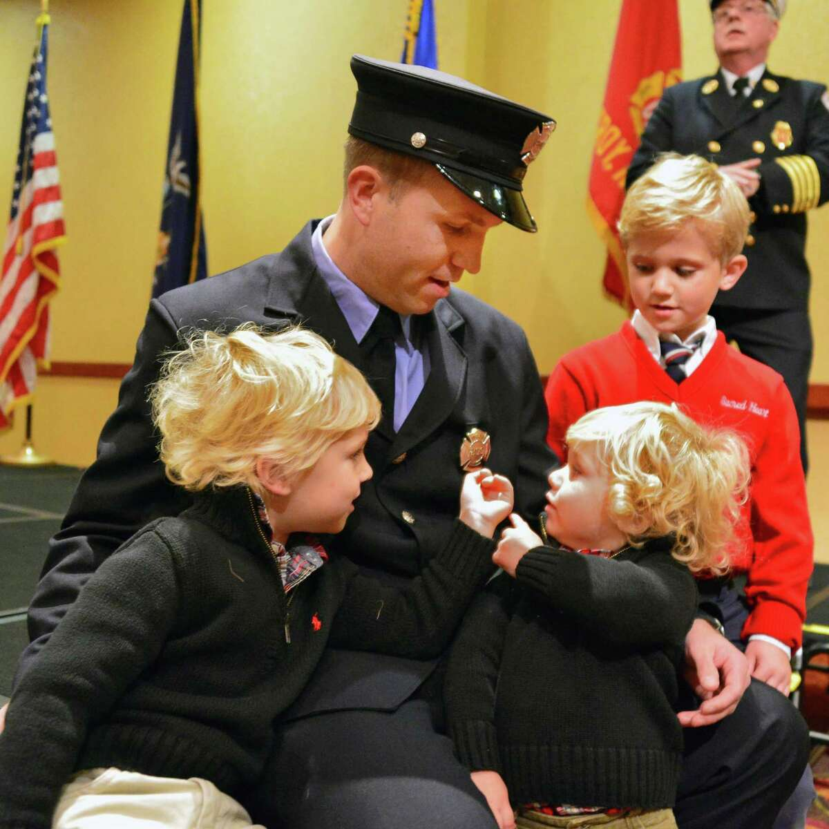 Troy firefighter Kevin Kilgallon with sons, from left, Braeden, 4, Max, 1, and Blake 6, before the start of a promotion ceremony where Kevin was sworn in as a lieutenant Tuesday, Nov. 19, 2013, in Troy, N.Y. (John Carl D'Annibale / Times Union)
