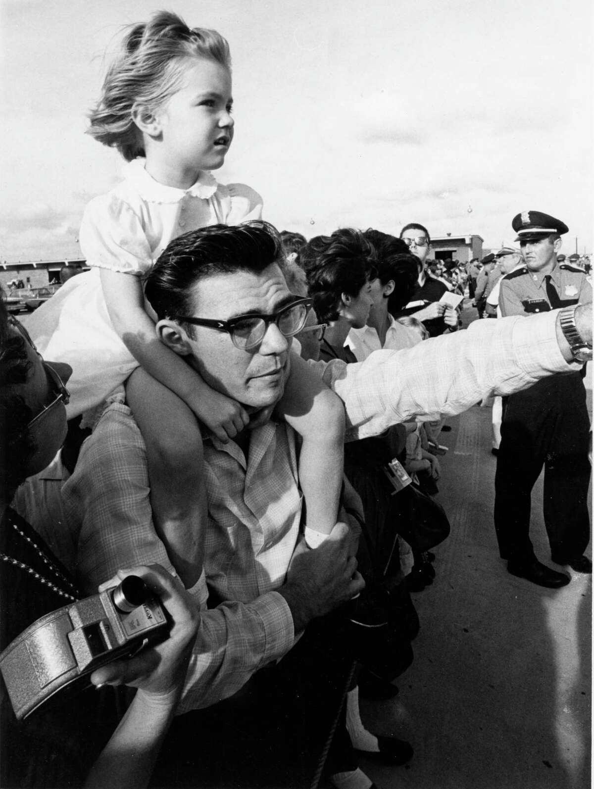 Large crowds waited at the airport and along the streets of Houston to greet Pres. Kennedy. Mike Arteberry of Alvin gives 4-year-old Rebeca Lee Stevens a better view from his shoulders as they await the arrival of the President's airplane.