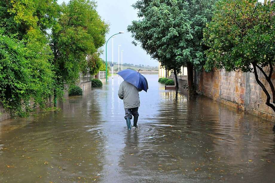 A villager wadesthrough a flooded street in Siliqua, Sardinia. Flash floods killed at least 14 people on the   Italian island as rivers surged over their banks, bringing down bridges and inundating neighborhoods. Photo: Angelo Cucca, AFP/Getty Images
