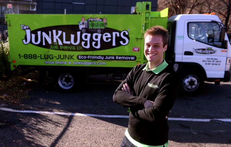 Josh Cohen, founder and CEO of Junkluggers, stands in front of one of his trucks at the company's Norwalk office. Photo: Autumn Driscoll / Connecticut Post