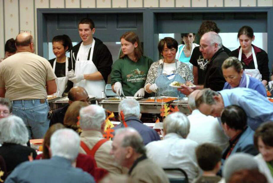 Volunteers prepare and serve hundreds of meals annually at the annual Thanksgiving Community Feast organized by Saugatuck Congregational Church. Photo: File Photo / Westport News