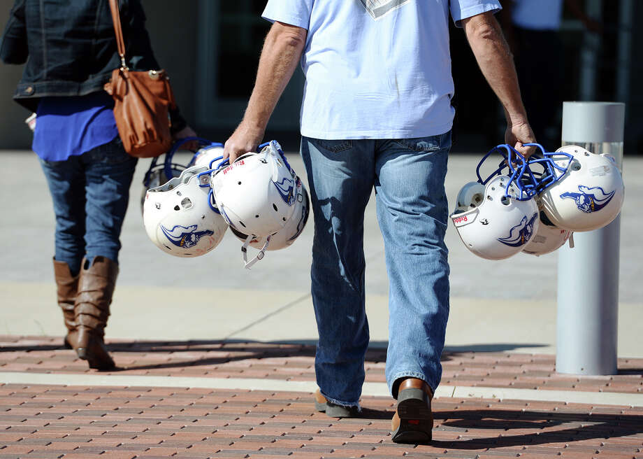 Stephanie Romero, left, and Rob Sjodin carry helmets into the Event Centre on Tuesday afternoon as they help prep for the West Beaumont Bulldogs Intermediate Football League banquet. According to Romero, a board member for the WBBIFL, the event will honor the 112 players and 11 cheerleaders, and is expected to have an attendance between 300 and 400 people. Photo taken Jake Daniels/@JakeD_in_SETX Photo: Jake Daniels / ©2013 The Beaumont Enterprise/Jake Daniels