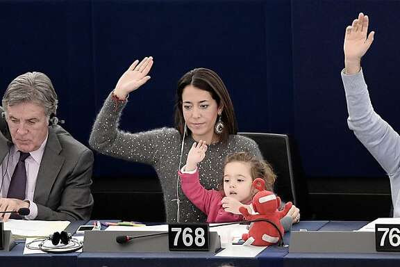 Italy's Member of the European Parliament Licia Ronzulli (center) takes part with her daughter Victoria in a vote during a plenary session of the European parliament, on November 19, 2013  in Strasbourg, eastern France.