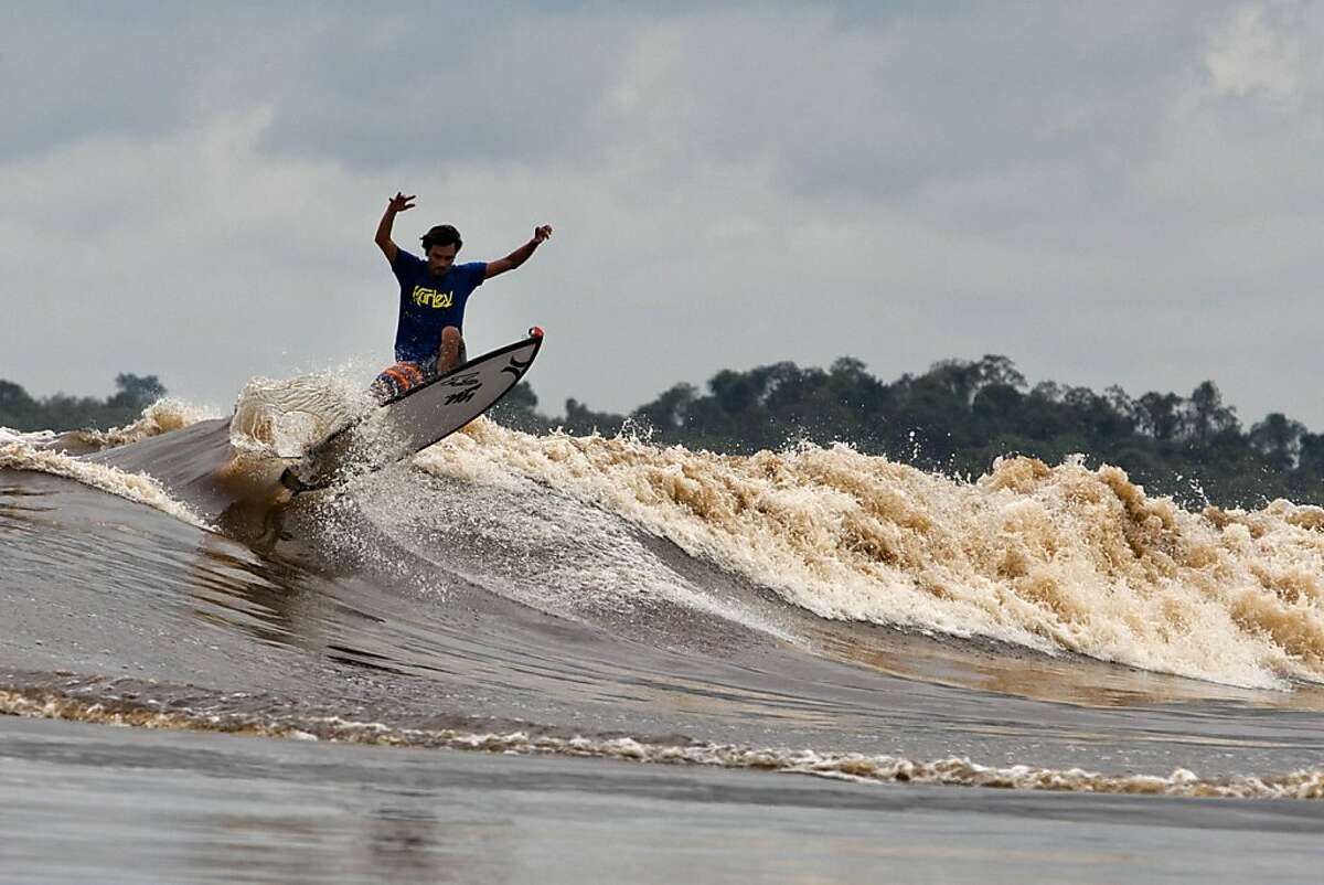 Don't fall, Marlon: Marlon Gerber surfs the Kampar River during the Bono tidal wave in Teluk Meranti, Sumatra. The tidal wave occurs throughout the year at certain days around the full moon and new moon, but is strongest during the rainy season when a single wave can travel up to 37 miles. Crocodiles live in the Kampar, which makes wiping out even more thrilling.