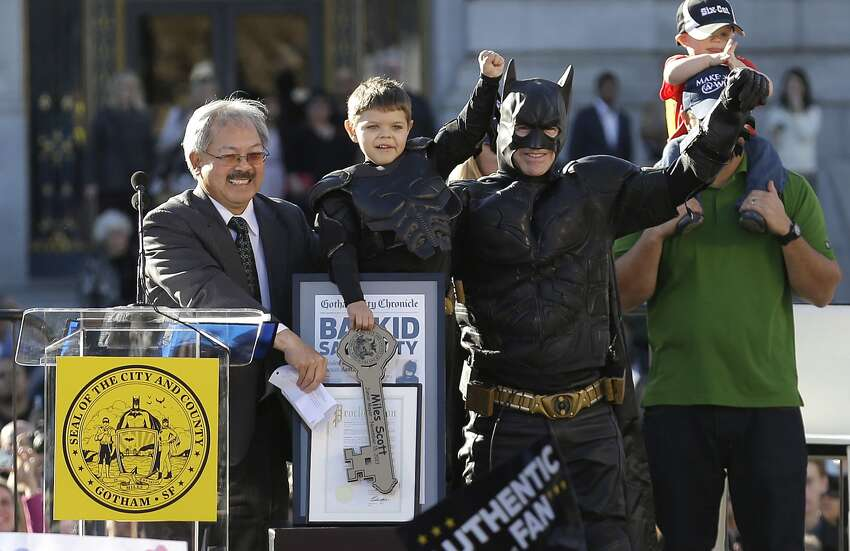 Miles Scott, dressed as Batkid, second from left, raises his arm next to Batman at a rally outside of City Hall with Mayor Ed Lee, left, and his father Nick and brother Clayton, at right, in San Francisco, Friday, Nov. 15, 2013. Scott was called into service on Friday morning by San Francisco Police Chief Greg Suhr to help fight crime, as San Francisco turned into Gotham City as city officials helped fulfill the 5-year-old leukemia patient's wish to be