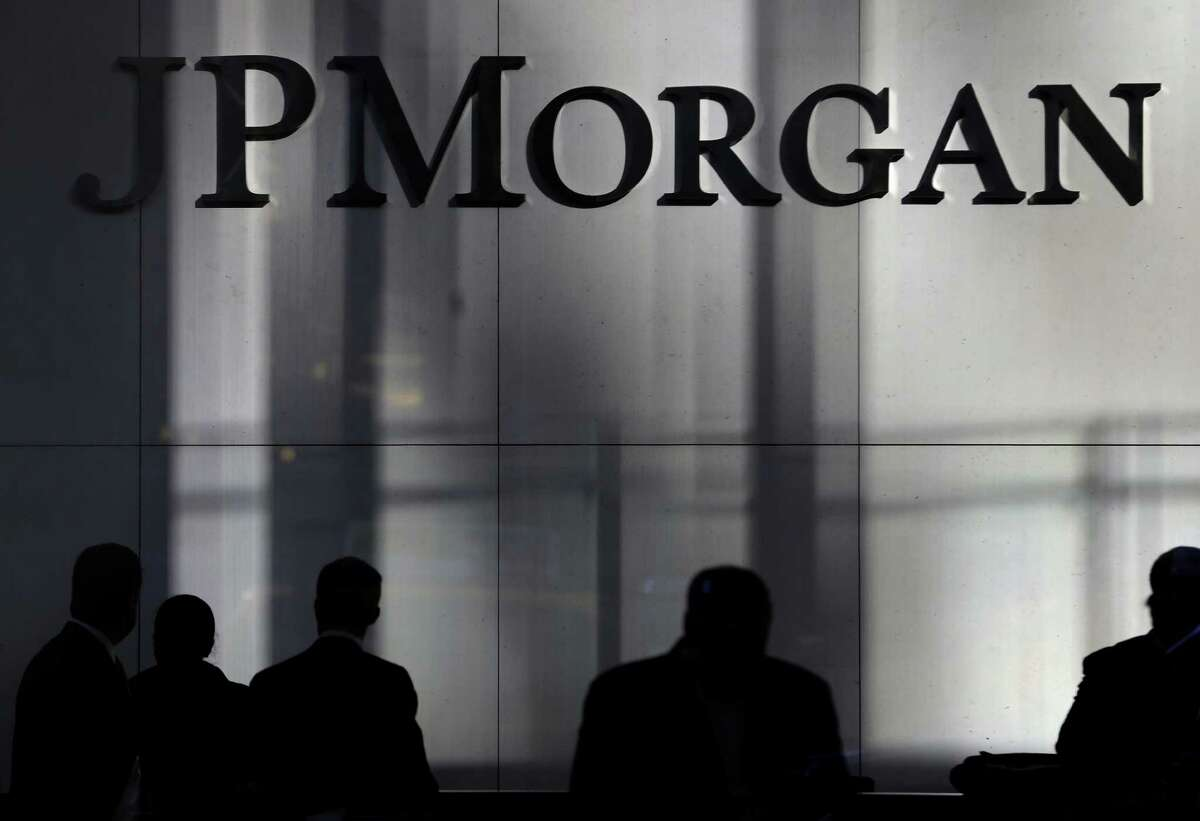 People are silhouetted below signage at the JPMorgan Chase & Co. headquarters in New York, Tuesday, Nov. 19, 2013. The Justice Department and JPMorgan Chase & Co. have settled all issues and could sign a $13 billion agreement as early as Tuesday that would be the largest settlement ever reached between the government and a corporation, a person familiar with the negotiations says. (AP Photo/Seth Wenig) ORG XMIT: NYSW104