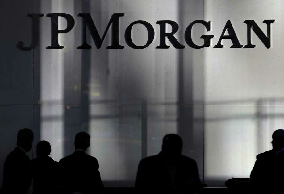 People are silhouetted below signage at the JPMorgan Chase & Co. headquarters in New York, Tuesday, Nov. 19, 2013. The Justice Department and JPMorgan Chase & Co. have settled all issues and could sign a $13 billion agreement as early as Tuesday that would be the largest settlement ever reached between the government and a corporation, a person familiar with the negotiations says. (AP Photo/Seth Wenig) ORG XMIT: NYSW104 Photo: Seth Wenig / AP
