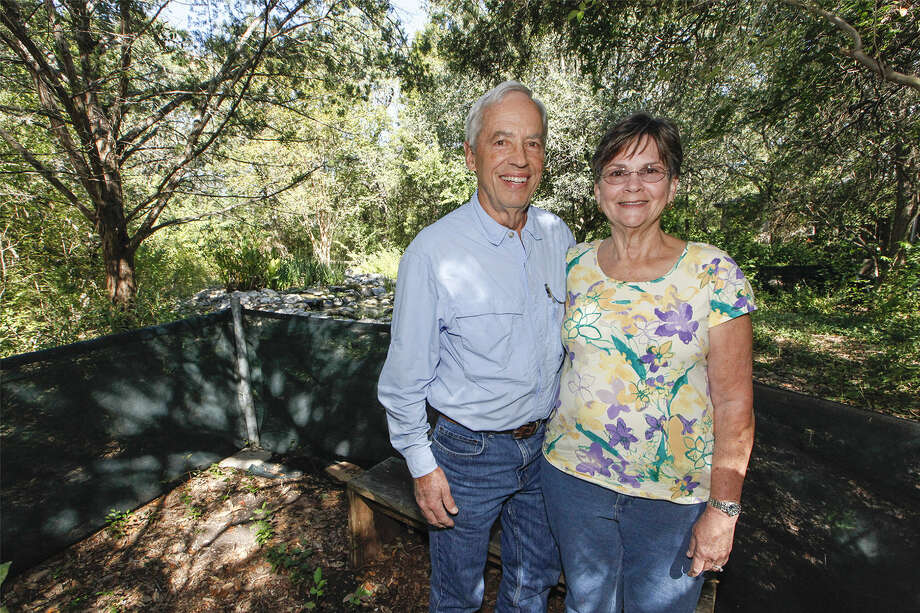 Don (left) and Susan Schaezler stand in the back yard of their home with a large water feature in the background at the Warbler Woods Bird Sanctuary. Photo: Marvin Pfeiffer / NE Herald