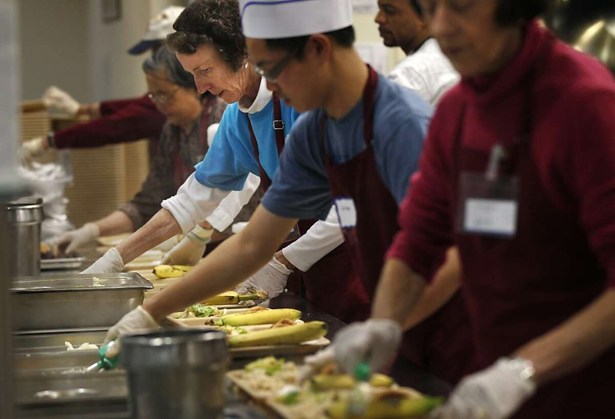 Cecilia Hurley, third from right, serves food for hundreds at St. Anthony Dining Room November 19, 2013 in downtown San Francisco. Every year St. Anthony's provides Thanksgiving meals to thousands of people. This year they are preparing to feed at least 4,000 people, their biggest year yet. St. Anthony's is having a Holiday Curbside Donation Drive, Nov. 23-28 and Dec. 21-24 to accommodate their holiday meals.