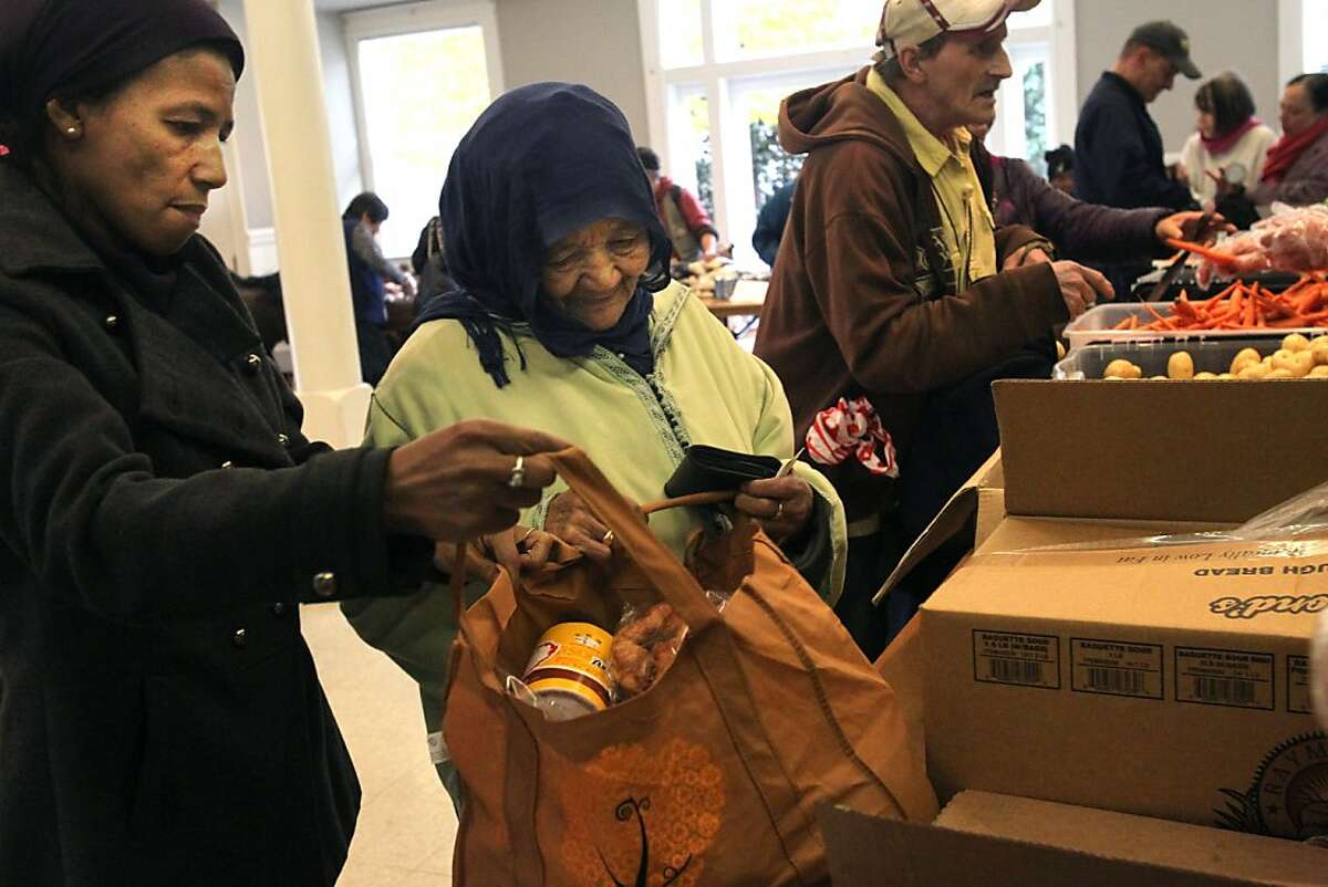 Ghaleb Milouda, left, helps her mother Mahjouba Benabou bag food during an 11:30am weekly food pantry at St. Francis Lutheran Church November 19, 2013 in the Castro District, San Francisco, Calif. The pantry is giving out certain holiday items in addition to their normal supply such as special chicken, desserts and canned cranberry. Donations are down this year, though, and there is concern they won't be able to meet the heightened demand.