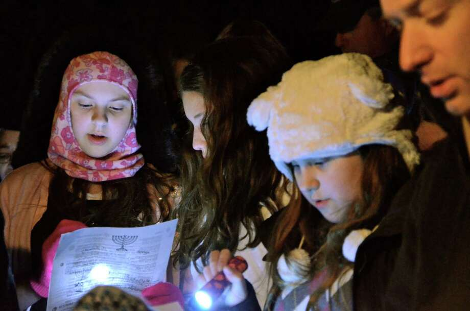 The New Canaan Menorah will be lit at 6 p.m. Wednesday, Nov. 27, on God's Acre. Above, Vanessa Kanter, Jessica Perrino, Lindsey Kanter and Dan Gropper sing at last year's lighting. Photo: Jeanna Petersen Shepard / New Canaan News