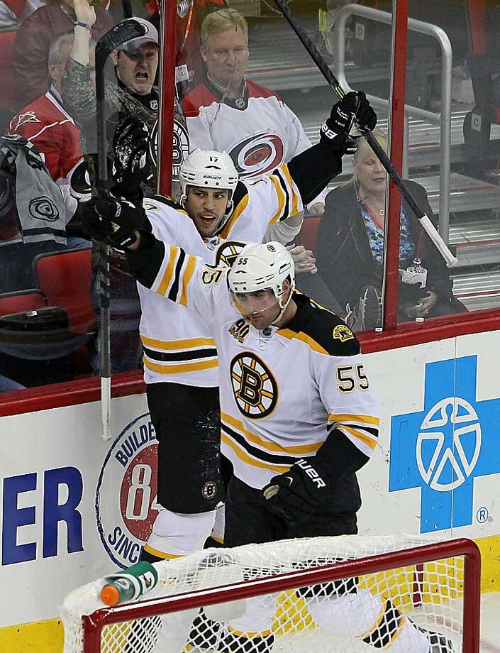 Boston Bruins' Milan Lucic (17) and Johnny Boychuk (55) celebrate Boychuk's goal during the third period of an NHL hockey game against the Carolina Hurricanes in Raleigh, N.C., Monday, Nov. 18, 2013. Boston won 4-1. (AP Photo/Karl B DeBlaker) Photo: Karl B DeBlaker, Associated Press