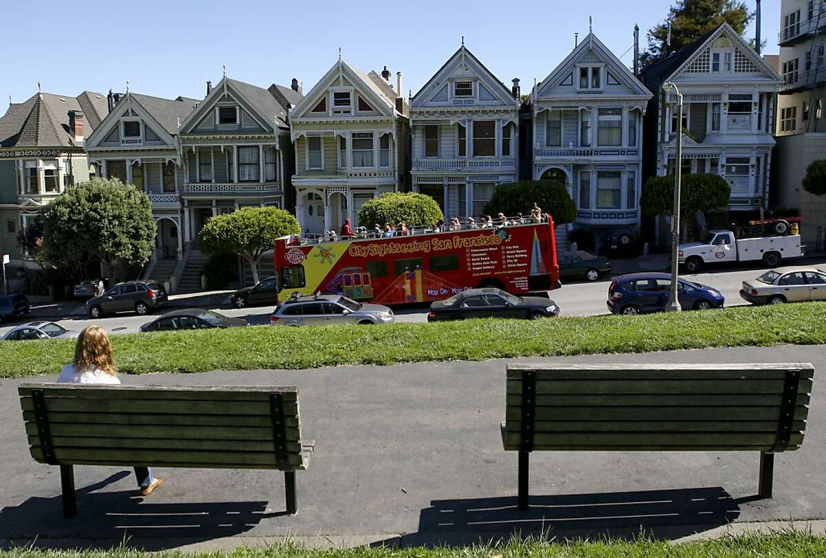 Rhonda Smith of Pennsylvania reads a book at Alamo Square Park as a tour bus passes by the Painted Ladies on Steiner Street on Thursday, Sept. 26, 2013.