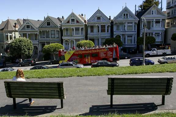 Rhonda Smith of Pennsylvania reads a book at Alamo Square Park as a tour bus passes by the Painted Ladies on Steiner st in San Francisco, Ca, on Thursday, Sept. 26, 2013.