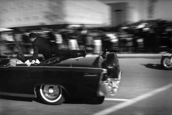 Secret Service agent Clinton Hill jumps on the back of the presidential limousine to shield first lady Jaqueline Kennedy on Nov. 22, 1963. Hill was long haunted by the day, blaming himself for not reacting quicker.