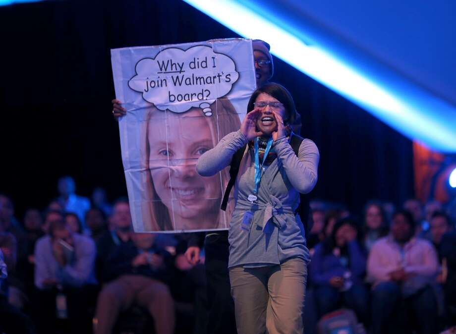 A protester shouts as Yahoo CEO Marissa Mayer speaks in conversation with Salesforce chairman and CEO Marc Benioff at the 2013 Dreamforce conference on November 19, 2013 in San Francisco, Calif. The annual Dreamforce conference runs through November 21. Photo: Justin Sullivan, Getty Images