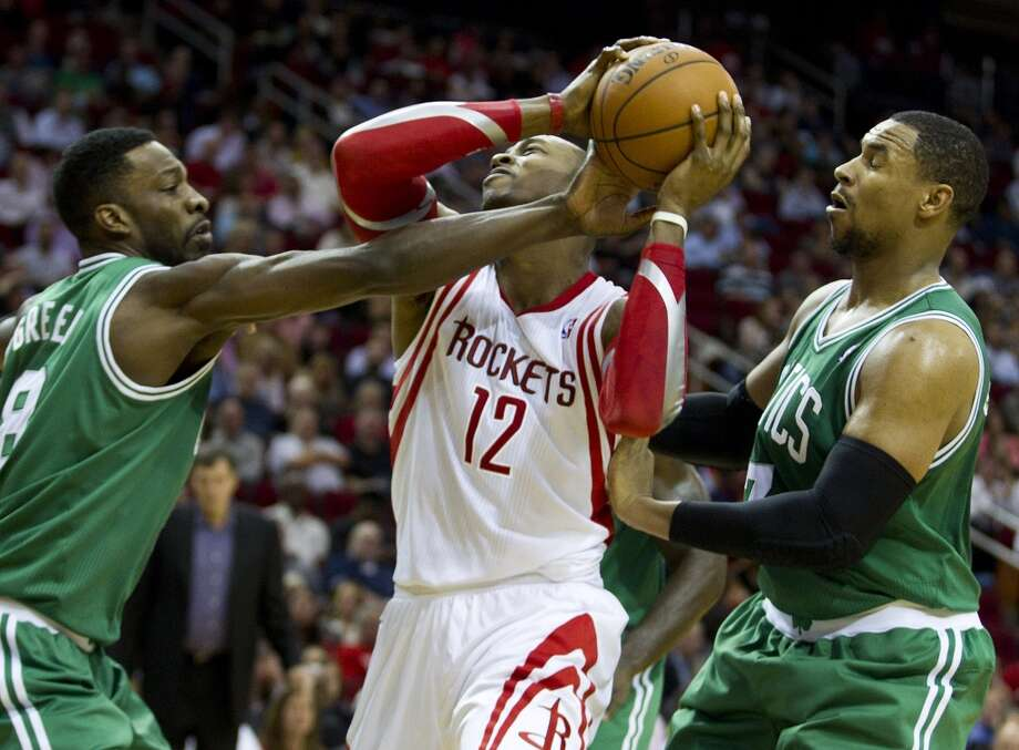 Rockets center Dwight Howard tries to keep possession between two Celtics defenders. Photo: Brett Coomer, Houston Chronicle