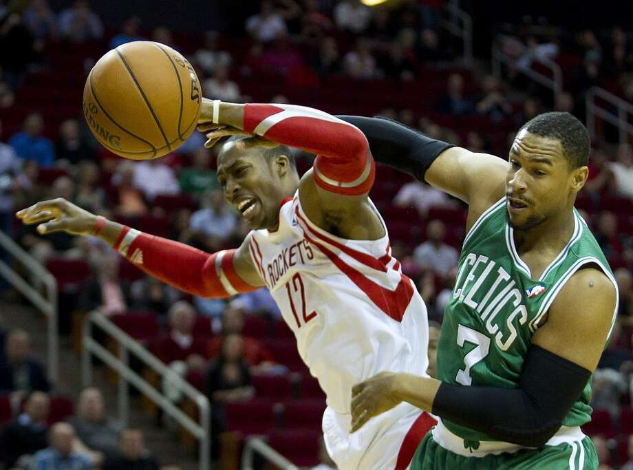 Jared Sullinger of the Celtics and Rockets center Dwight Howard get tangled up fighting for a rebound. Photo: Brett Coomer, Houston Chronicle