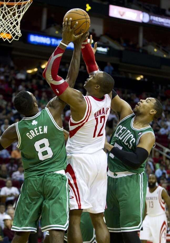 Rockets center Dwight Howard tries to attempt a shot between two Celtics defenders. Photo: Brett Coomer