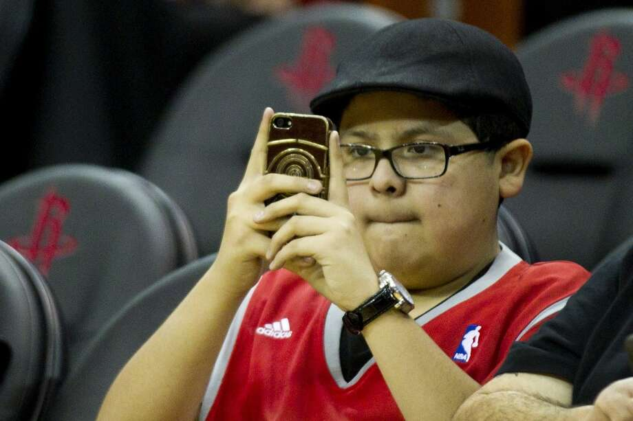 Actor Rico Rodriguez ho plays Manny Delgado on television's 'Modern Family' watches the Rockets warm up before they face the Celtics. Photo: Brett Coomer, Houston Chronicle