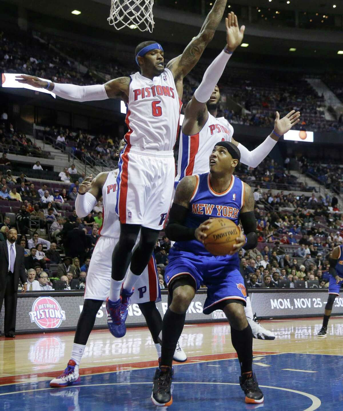 New York Knicks forward Carmelo Anthony (7) is blocked by Detroit Pistons forwards Josh Smith (6) and Greg Monroe, rear right, during the first half of an NBA basketball game in Auburn Hills, Mich., Tuesday, Nov. 19, 2013. (AP Photo/Carlos Osorio) ORG XMIT: MICO104