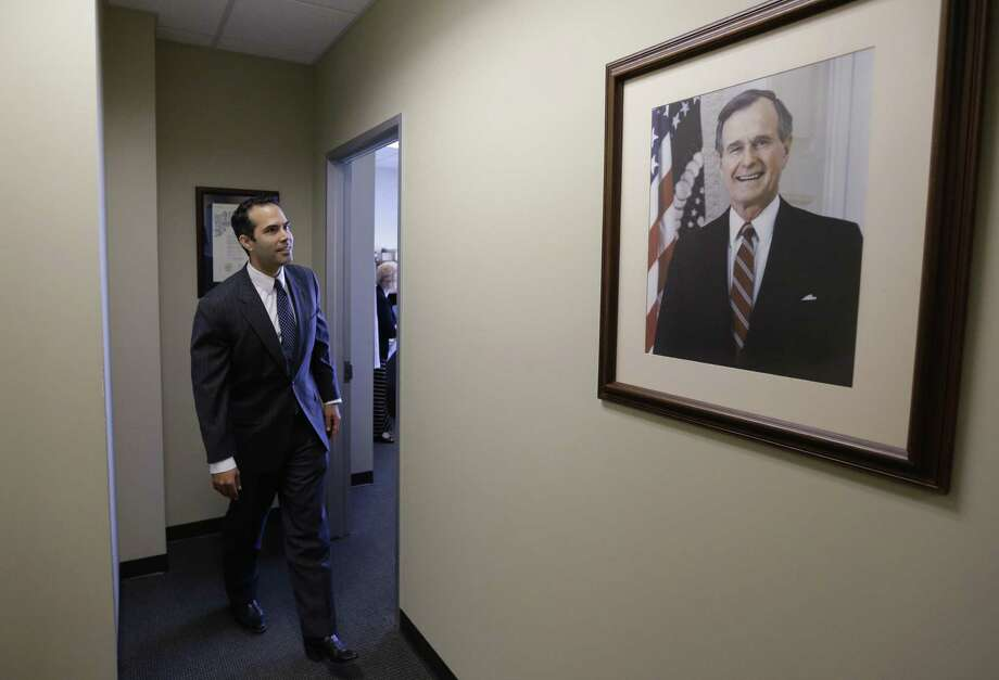 George P. Bush walks near a portrait of his grandfather, George H.W. Bush, at the Republican Party of Texas headquarters in Austin, where he filed to run for Texas land commissioner. Photo: Eric Gay / Associated Press