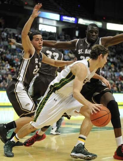 Siena's Rob Poole works his way around St. Bonaventure defenders during their men's college basketba