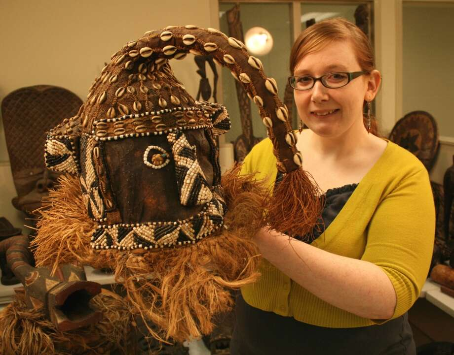 Online sales appraiser Jazlan Grigsby holds up a bead and cowrie Kuba Mukenga Tribal Mask. The Kuba Kingdom artifact represented the power of the elephant through a trunk-like extension. Photo: Photo From Goodwill