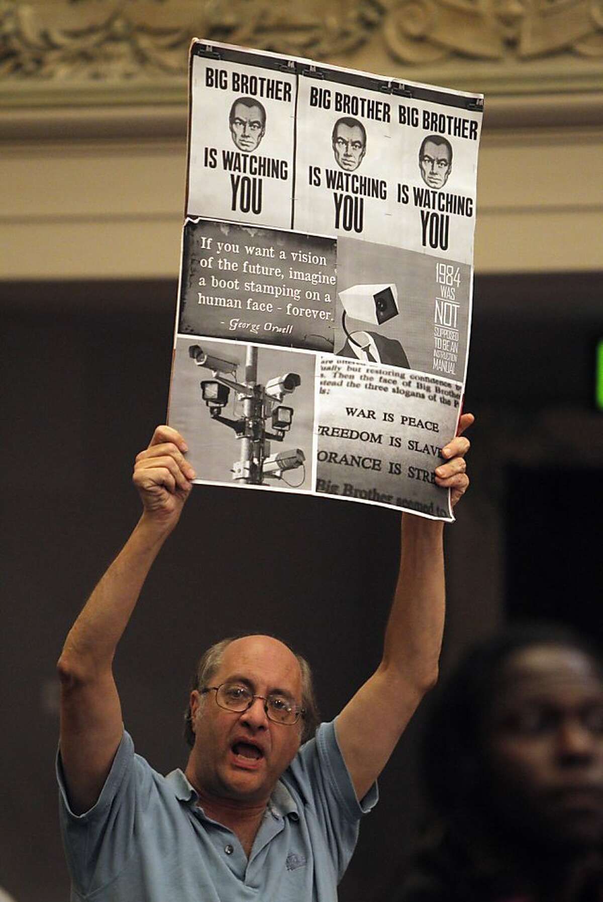 J.P. Massar holds a sign showing his opposition to the DAC as several Oakland residents opposed to the planned Domain Awareness Center in Oakland, Calif., interrupted the Oakland City Council meeting on Tuesday, November 19, 2013 to move the agenda item up earlier. The council planned Tuesday to move ahead with the DAC , which the city says it a federally funded center to help them better monitor crime and protests but critics call the