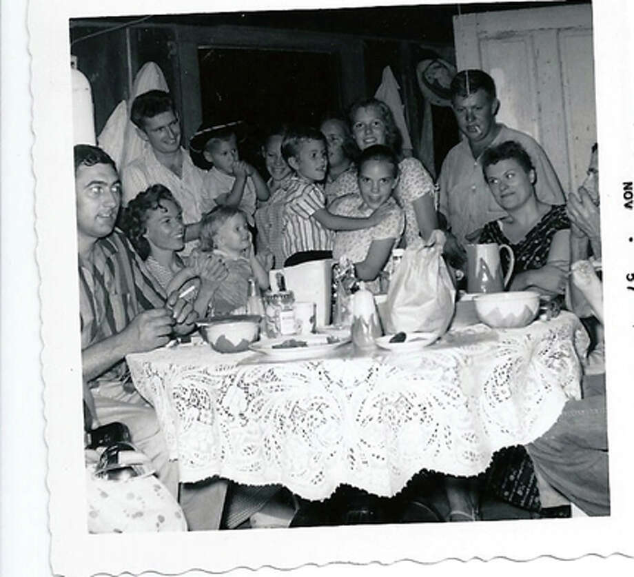 "Jesse Raglin Family Nov 1957, brother Dave was on his way to new Navy duty station, so all of Dad's 9 children were ""home"" for the first time, (2 didn't get in this picture). That's Dave and his wife Jeannie looking at each other across the table.  Virginia Culp"