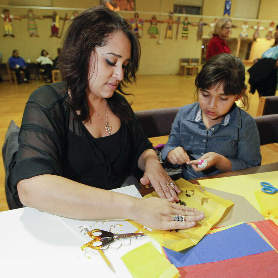 Mercedes Ortega and her daughter Kayle, 7, make papel picado during a class at Our Lady of the Lake University's International Folk Culture and Dance Center.