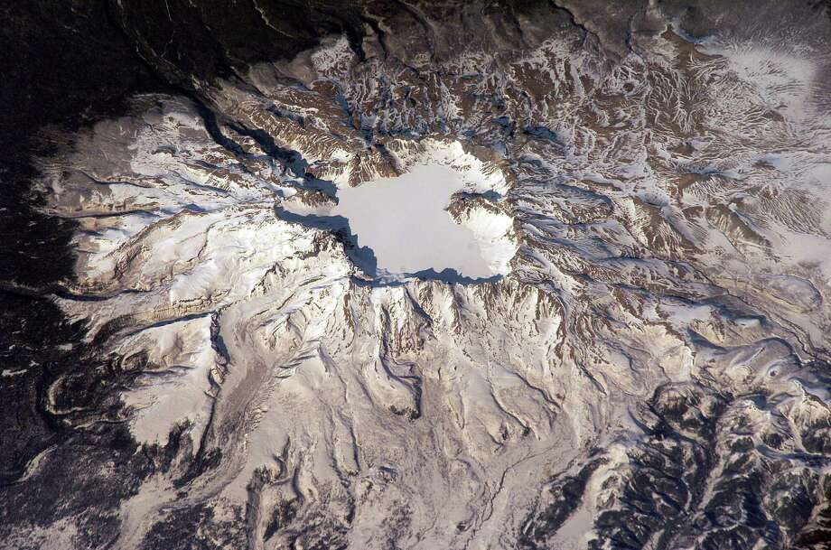 April 4, 2003 — This view featuring Baitoushan Volcano, China and North Korea, was photographed by an Expedition 6 crewmember on the International Space Station (ISS). One of the largest known Holocene eruptions occurred at Baitoushan Volcano (also known as Changbaishan in China and P'aektu-san in Korea) about 1000 A.D., with erupted material deposited as far away as northern Japan – a distance of approximately 1200 kilometers. The eruption also created the 4.5 kilometer diameter, 850 meters deep summit caldera of the volcano that is now filled with the waters of Lake Tianchi (or Sky Lake). This oblique photograph was taken during the winter season, and snow highlights frozen Lake Tianchi along with lava flow lobes along the southern face of the volcano. Baitoushan last erupted in 1702 and is considered a dormant volcano. Gas emissions were reported from the summit and nearby hot springs in 1994, but no evidence of renewed activity of the volcano was observed. The Chinese-Korean border runs directly through the center of the summit caldera, and the mountain is considered sacred by the dominantly Korean population living near the volcano. Lake Tianchi is a popular resort destination, both for its natural beauty and alleged sightings of unidentified creatures living in its depths (similar to legendary Loch Ness Monster in Scotland). Photo: NASA