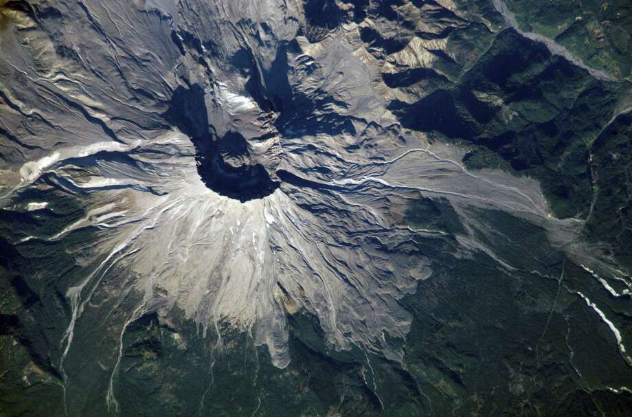 October 25, 2002 —  Mount Saint Helens, Washington, is featured in this image photographed by an Expedition 5 crewmember on the International Space Station (ISS). On May 18, 1980, Mount Saint Helens volcano erupted. A series of earthquakes preceded the eruption, triggering a collapse of the north side of the mountain into a massive landslide. This avalanche coincided with a huge explosion that destroyed over 270 square miles of forest in a few seconds, and sent a billowing cloud of ash and smoke 80,000 feet into the atmosphere. The crewmembers on the Station captured this detailed image of the volcano's summit caldera. In the center of the crater sits a lava dome that is 876 feet above the crater floor and is about 3,500 feet in diameter. The upper slopes of the 1980 blast zone begin at the gray colored region that extends north (upper left) from the summit of the volcano. The deeply incised valley to the left (west) is the uppermost reach of the South Fork of the Toutle River. Devastating mudslides buried the original Toutle River Valley to an average depth of 150 feet, but in places up to 600 feet. The dark green area south of the blast zone is the thickly forested region of the Gifford Pinchot National Forest. Photo: NASA