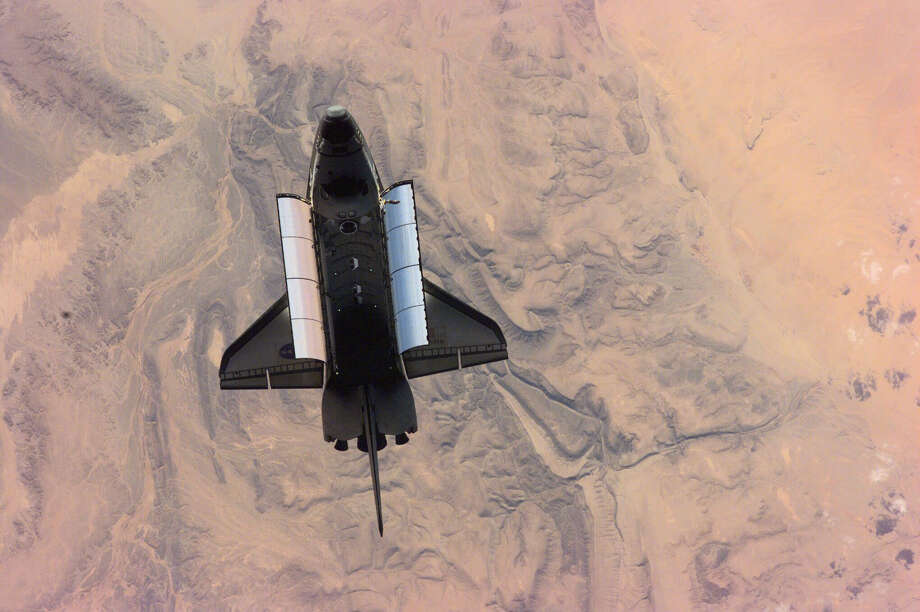 February 26, 2001 — This high-angle image of the Space Shuttle Atlantis backdropped over a desert was photographed by the three-man Expedition One crew aboard the International Space Station (ISS) shortly after the shuttle and the outpost unlinked following several days of joint operations of the two crews. The scene was recorded with a digital still camera. Photo: NASA