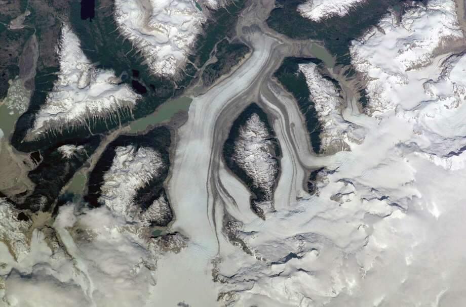 December 2000 — This nadir view of a Chilean glaciated area was provided by one of the early December digital still camera images down linked from the International Space Station (ISS) to ground controllers in Houston. The remote headwaters of the Rio de la Colonia are located on the eastern flank of the Cerro Pared Norte, a high, coastal range of the Andes in southern Chile. This is but a portion of a larger glaciated region of the Chilean coast located at only 47 degrees south latitude. The river actually begins its flow just off the top of this scene at the foot of the two large, converging, valley glaciers near the center. Some of the numerous lakes visible are tinted by the fine glacial sediments suspended in their waters. Note the shards of ice that have calved from the glaciers into the lakes on the left. Also note the shadows of the crest of the over 14,000-foot mountains (lower center). The remote headwaters of the Rio de la Colonia are located on the eastern flank of the Cerro Pared Norte, a high, coastal range of the Andes in southern Chile. This is a but a portion of a larger glaciated region of the Chilean coast located at only 47 degrees south latitude. The river actually begins its flow just off the top of this scene at the foot of the two large, converging, valley glaciers near the center. Some of the numerous lakes visible are tinted by the fine glacial sediments suspended in their waters. Note the shards of ice that have calved from the glaciers into the lakes on the left. Also note the shadows of the crest of the over 14,000-foot mountains (lower center). Photo: NASA