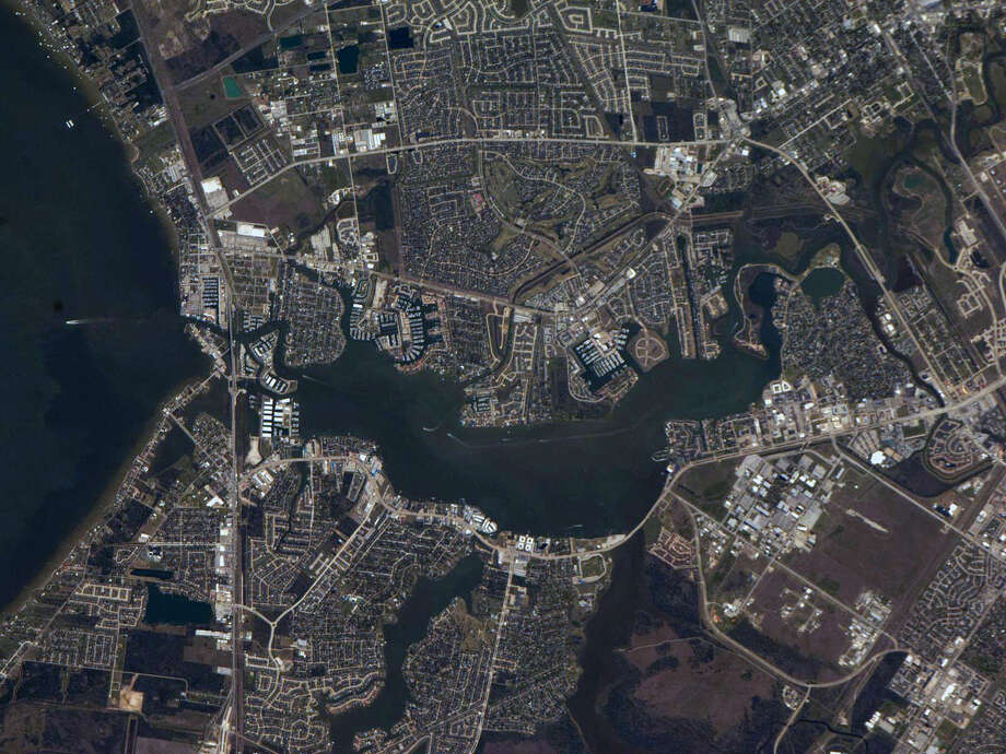 "March 12, 2013 — One of the Expedition 34 crew members aboard the Earth-orbiting International Space Station captured this high oblique image of the environs of NASA's 1625-acre Johnson Space Center (clearly seen in the lower right quadrant of the image). NASA Parkway can be traced from the space complex eastward almost to Galveston Bay. Though spring had not quite yet arrived, this particular week sported extremely clear skies and warmer than normal temperatures for so-called ""spring-breakers."" Photo: NASA"