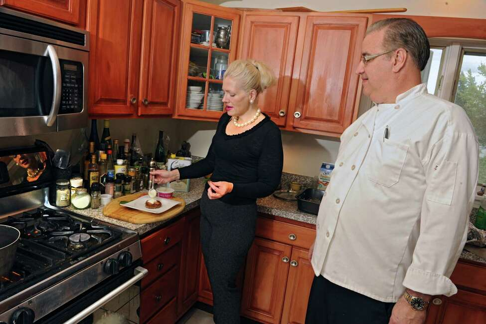 Stacey Morris and her boyfriend Bill Duckman cook a Thanksgiving dinner that incorporates both Christian and Jewish traditions on Friday, Nov. 1, 2013 in Loudonville, N.Y. Here Morris adds a dollop of creme fraiche to a potato latke. (Lori Van Buren / Times Union)