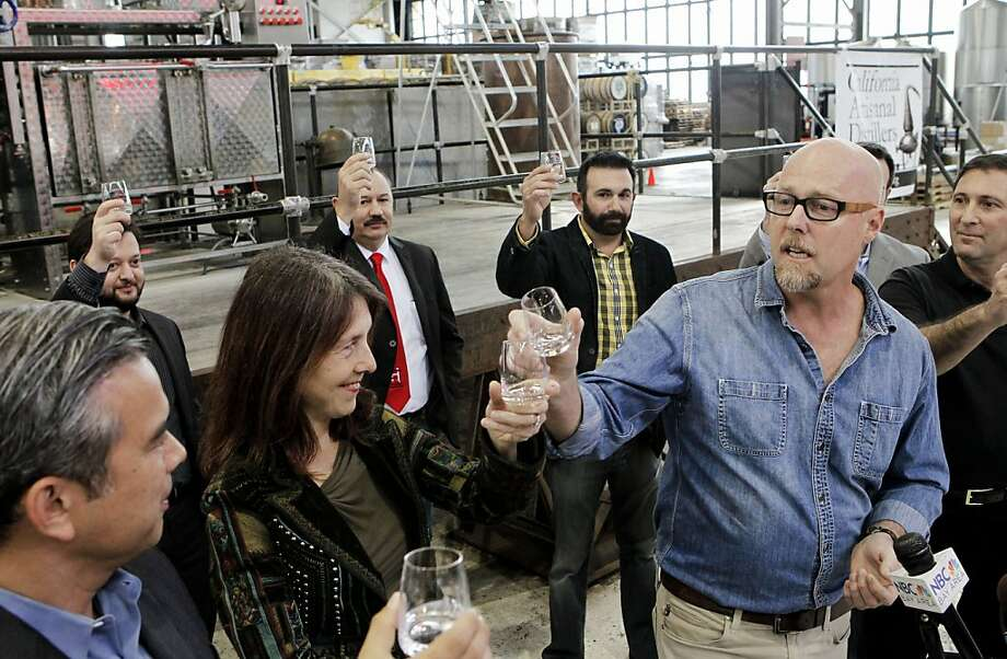 Assembly members Rob Bonta, D-Alameda (left), and Nancy Skinner, D-Berkeley, raise their glasses to Lance Winters, the master distiller at St. George Spirits in Alameda. Photo: Michael Macor, The Chronicle
