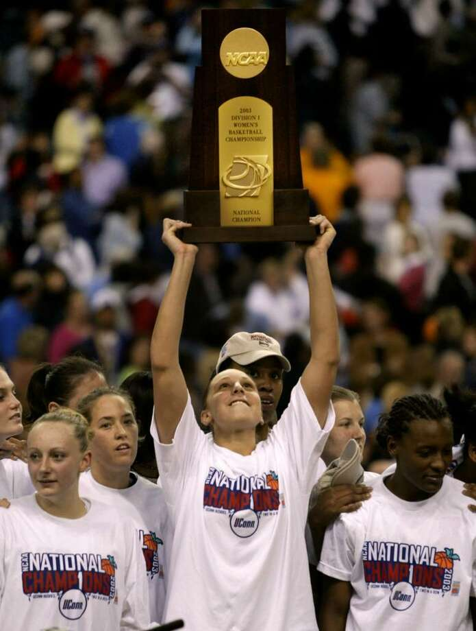 Connecticut guard Diana Taurasi holds up the trophy after their 73-68 win over Tennessee in the NCAA Women's Final Four championship game on Tuesday, April 8, 2003, in Atlanta. Taurasi scored 28 points to lead Connecticut. From left are Maria Conlon, Ashley Valley, Taurasi, and Ashley Battle, right. (AP Photo/Chuck Burton) Photo: CHUCK BURTON, AP / AP